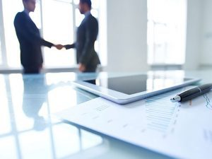 business-shaking-hands-with-tablet-and-chart-in-front_istock_gl497x373